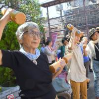 Seniors exercise Monday during a health promotion event for Respect for the Aged Day at Koganji Temple in Tokyo's Sugamo neighborhood. The street near the temple is known as a popular shopping area for seniors. | SATOKO KAWASAKI