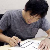 Dwango Co., Ltd. Director Shigetaka Kurita writes a pictograph during an interview at his office in Tokyo on Sept. 14. The Japanese creator of the first emoji wanted to add nuance to mobile phone messages and never imagined his 1999 work would become a global phenomenon. | AP