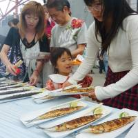 Women prepare saury. A Japanese research team has found that people who eat fish frequently, especially blue fish, face a lower risk of depression than those consuming less. | KYODO