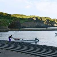 Fishermen return to a port in Okushiri Island, Hokkaido, on the morning of July 29 after a North Korean missile test the previous day. | KYODO