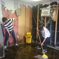 Yuki Sato (left) and Natsuki Igarashi sweep mud and water out of a restaurant flooded by Hurricane Harvey in Houston. | FUKUSHIMA MINPO