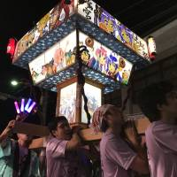 People carry a special portable shrine designed with characters from the anime title 'Lucky Star' during a festival held in the city of Kuki, Saitama Prefecture, on Sunday. The city is featured in the anime, which was first broadcast in 2007. | KAZUAKI NAGATA