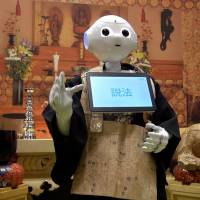 Pepper, the humanoid robot created by SoftBank Robotics, recites Buddhist sutras during the Life Ending Industry Expo 2017 in Tokyo on Aug. 23. | KAZUHIRO KOBAYASHI