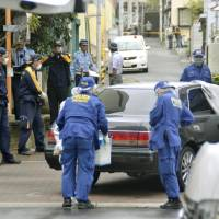 Police officers investigate the site where a former member of the Kobe Yamaguchi-gumi yakuza group was shot dead on Tuesday morning in the city. | KYODO