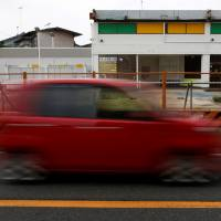 A car drives past a closed gas station in Chiba Prefecture on June 28. With waning demand for gasoline, the number of gas stations nationwide has roughly halved from a 1995 peak, leaving many mainly elderly people in remote areas a long way from the nearest pump to fill up.   REUTERS