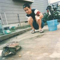 Imazu as a child plays with his pet turtle at home in the city of Chiba in 1998. | COURTESY OF TAKESHI IMAZU