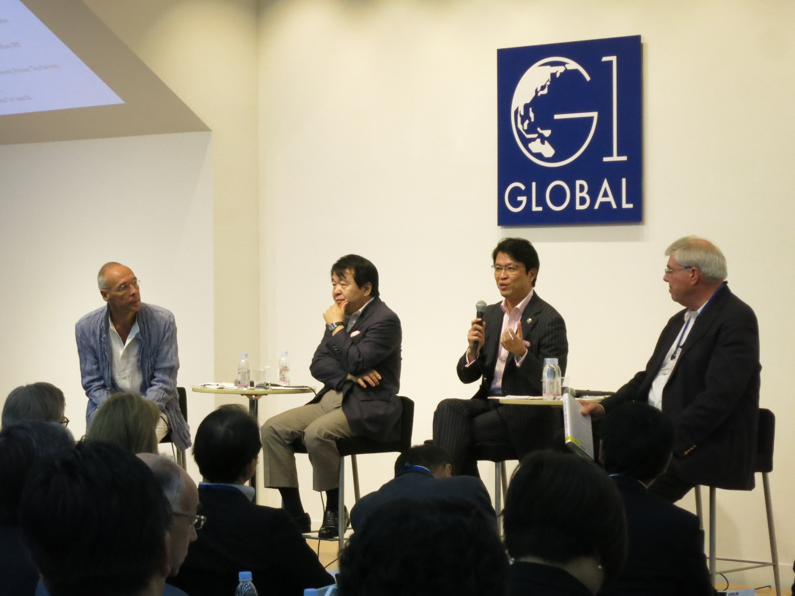 Hiromichi Mizuno (third from left), chief investment officer at GPIF, speaks during a session of the G1 Global Conference at Globis University in Tokyo on Monday. Other panelists (from left) are Jesper Koll, CEO of Wisdom Tree Japan; Heizo Takenaka, professor emeritus at Keio University; and Richard McCormack, senior adviser at the Center for Strategic and International Studies. | KAZUAKI NAGATA