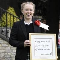 Gracie Starkey, a 14-year-old student at Wycliffe College in Gloucestershire, England, holds up her winning entry to beverage maker Ito En's annual haiku competition at her school on Sept. 11. | KYODO