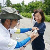 A worker at Sompo Japan Nipponkoa Himawari Life Insurance Inc. gets her body temperature measured during a walking program in Kaminoyama, Yamagata Prefecture, in July. | KYODO