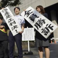 People hold up banners proclaiming victory in front of the Tokyo District Court on Friday after it ordered Japan Post Co. to compensate three contract workers who sued for being compensated less than full-time employees doing the same work. | KYODO