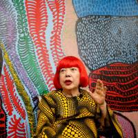 Avant-garde artist Yayoi Kusama, 88, speaks to the media at her studio in Tokyo on Tuesday. Kusama, whose exhibitions have been among the hottest tickets in the art world, is now opening a museum in downtown Tokyo dedicated to her paintings and sculptures. | REUTERS