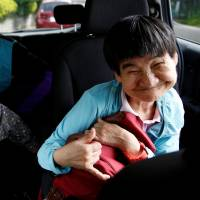 Congenital Minamata disease patient Shinobu Sakamoto, 61, and her mother, Fujie, sit in a car as they head for a hospital in Minamata, Kumamoto Prefecture, on Sept. 14. | REUTERS
