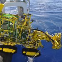 A mining machine is put into water off the coast of Okinawa Tuesday to extract minerals from a deep-water seabed. | AGENCY FOR NATURAL RESOURCES AND ENERGY / VIA KYODO