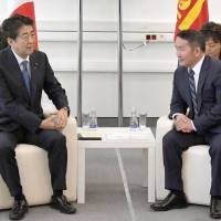 Prime Minister Shinzo Abe speaks with Mongolian President Khaltmaa Battulga at an economic forum in Vladivostok, Russia, on Thursday. Abe's two-day visit to the city also includes talks with Russian President Vladimir Putin and South Korean President Moon Jae-in. | KYODO