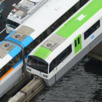 A monorail train on the right is seen stranded due to a power outage Tuesday in a section between Showajima and Seibijo stations near Haneda airport in Tokyo. | KYODO