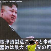 A man photographs an image of North Korean leader Kim Jong Un that appeared on a giant monitor in Tokyo last month. | AP