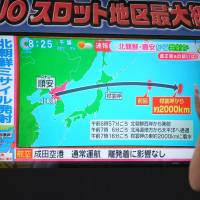 Pedestrians in Tokyo look at a TV screen broadcasting news of a North Korean missile that passed over Hokkaido early Friday morning. | AFP-JIJI