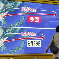 A news program on a public monitor in Sapporo compares North Korea's Friday missile launch over Japan with an earlier one on Aug. 29. | KYODO