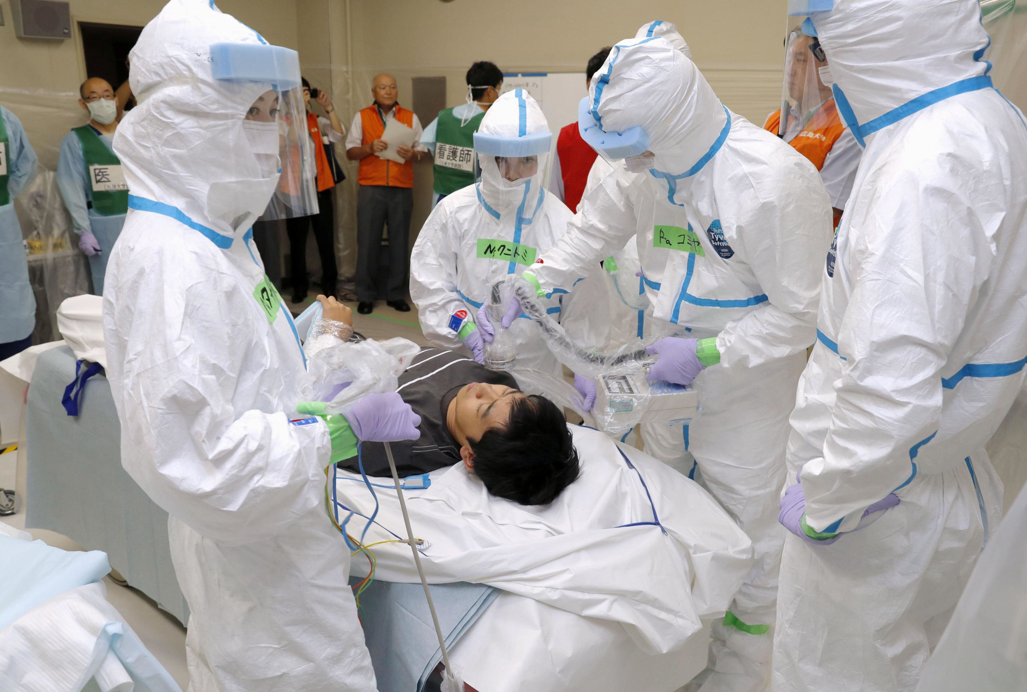 Doctors and a person pretending to be a radiation-contaminated patient participate in a nuclear drill at Kyushu University Hospital in Fukuoka on Sunday. The scenario assumes that the Genkai nuclear plant in Genkai, Saga Prefecture, is facing a core meltdown. | KYODO