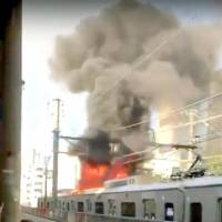 A screenshot of a YouTube video posted Sunday shows flames and smoke rising from the roof of an Odakyu Electric Railway Co. train in Shibuya Ward, Tokyo. | KYODO