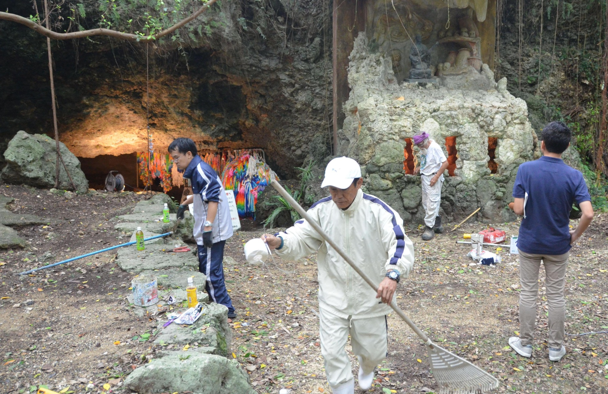 Relatives of Okinawans forced to commit mass suicide in the closing days of World War II clean the Chibichirigama cave, where the suicides took place and where acts of vandalism were discovered earlier this week, in the village of Yomitan on Saturday. | KYODO