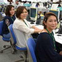 Bus tour guides work at Relia Inc.'s call center in Naha's Omoromachi district during their company's off-season. | OKINAWA TIMES