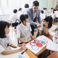 Students at Suginami Municipal Ogikubo Junior High School create their own Olympic logos in a special English class on July 8. | KYODO