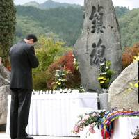 Families of the victims of the eruption at Mount Ontake Wednesday pray before a monument set up in the village of Otaki, Nagano Prefecture. | KYODO