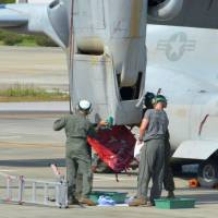 U.S. military personnel check an engine of a MV-22 Osprey aircraft Saturday morning at New Ishigaki Airport on the island in Okinawa Prefecture after it made an emergency landing there the previous day. | KYODO