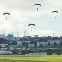The U.S. military conducts a parachuting drill on Thursday at Kadena Air Base in Okinawa Prefecture despite demands by the central and local governments that the drill be canceled. | KYODO