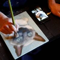 A painter paints a portrait of a pet cat at Pet Rainbow Festa, a pet funeral expo held in Tokyo on Monday. | REUTERS