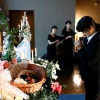 A staff prays in front of an altar for a pet dog during a demonstration of pet funeral services at the Pet Rainbow Festa, a pet funeral expo targeting an aging pet population, in Tokyo on Sept. 18. | REUTERS