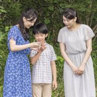 Prince Hisahito speaks with his sisters, Princesses Kako (left) and Mako, on Aug. 14 on the grounds of the Akasaka Detached Palace in Tokyo. | IMPERIAL HOUSEHOLD AGENCY / VIA KYODO