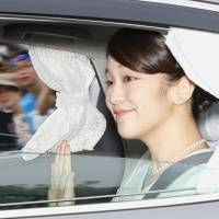 Princess Mako, the eldest granddaughter of Emperor Akihito, leaves the Imperial Palace on Sunday afternoon. The Imperial Household Agency announced her engagement to Kei Komuro, her longtime boyfriend from her university days, the same day. | POOL / VIA KYODO