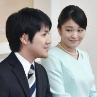 Princess Mako, the eldest granddaughter of Emperor Akihito and Empress Michiko, looks at her fiance, Kei Komuro, during a news conference in Tokyo on Sunday at which their engagement was officially announced. The two are expected to marry in fall next year. | KYODO