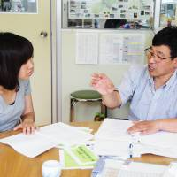 Asuka Chiba (left), a member of a group promoting relocation to rural Kyoto, and Kenji Kono, a regional promotion leader from the city of Nantan, hold a meeting in Nantan on June 20 on how to support urban dwellers seeking new lives in Kyoto's countryside. | KYODO