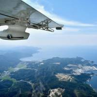 The Shimane Peninsula is seen from a seaplane during a test flight in July. The operator of the seaplane plans to offer flights linking the Sanin and Sanyo regions. | KYODO
