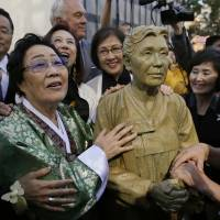 Former 'comfort woman' Lee Yong-soo, 89, of South Korea stands by a statue of Kim Hak-sun  that was unveiled in San Francisco on Friday. Kim was the first to break silence about Japan's forced wartime prostitution, in 1991. | AP