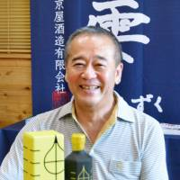Shinichiro Watanabe, president of Kyoya Distiller & Brewer Co., talks about Yuzu Gin, a gin made from sweet potatoes flavored with local citrus fruit, on Aug. 10 in Nichinan, Miyazaki Prefecture. | KYODO