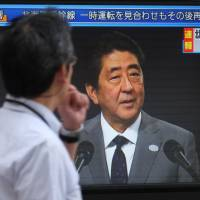 A pedestrian walks past a television screen in Tokyo broadcasting a news report showing Prime Minister Shinzo Abe on Friday after North Korea launched an intermediate-range missile over Japan. | AFP-JIJI