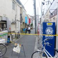 A police officer asks questions behind a crime scene tape where a teenage girl was stabbed allegedly by her boyfriend on Wednesday in Edogawa Ward, Tokyo. | KYODO