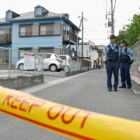 Police officers stand guard Monday by an apartment in Soka, Saitama, where a teenager was stabbed to death. The victim's girlfriend was also injured seriously in the attack, which was allegedly carried out by her former boyfriend. | KYODO
