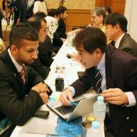 Saudi Arabian students are briefed about work opportunities at a job fair in Tokyo organized by the Saudi Arabian Embassy on March 13, 2014. About 30 companies participated. | KYODO