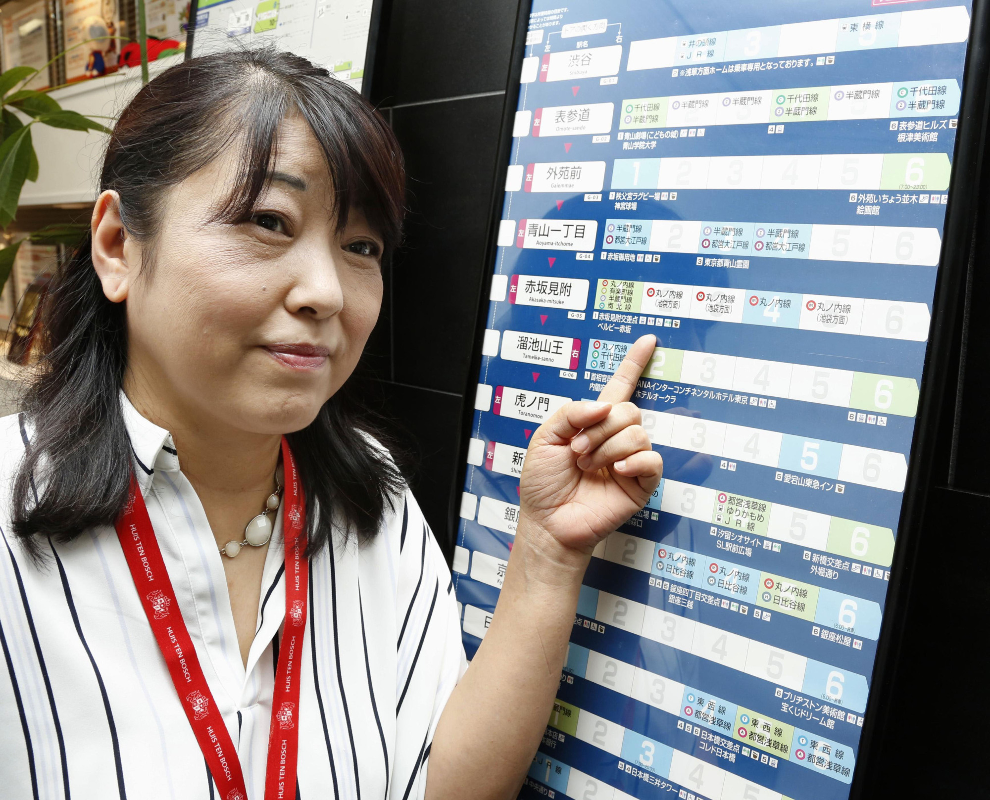 Navit President Yasuyo Fukui points to a subway car guide poster in Tokyo on Aug. 24. | KYODO