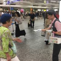 Railway company staff hand out packets of pocket tissues Tuesday at Yokohama station as part of a campaign asking the public to offer help to fellow commuters in need. | ALEX MARTIN