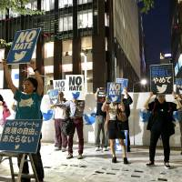Protesters rally in front of Twitter Japan's headquarters in Tokyo's Chuo Ward on Sept. 8, urging the social networking service to eliminate hate speech from its website. The demonstrators stand on top of 400 abusive tweets printed and pasted onto the street.   DAISUKE KIKUCHI