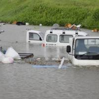 Vehicles are marooned when the Ono River in Oita Prefecture overflowed its banks on Sunday after Typhoon Talim moved across Kyushu and on to Shikoku. | KYODO