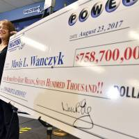Mavis Wanczyk, of Chicopee, Massachusetts, stands by a poster of her winnings during a news conference where she claimed the $758.7 million Powerball prize at Massachusetts State Lottery headquarters, Thursday in Braintree. Officials said it is the largest single-ticket Powerball prize in U.S. history. At left is state Treasurer Deb Goldberg. | AP