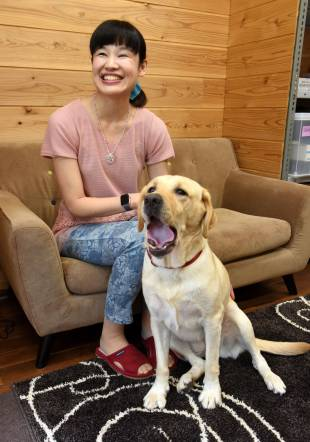 Kanako Suzuki sits with her guide dog, Ariel, in August.