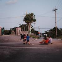 All in together: Neighborhood kids pull nature guide and surf instructor Ikkei Suzuki along on a skateboard. | LANCE HENDERSTEIN